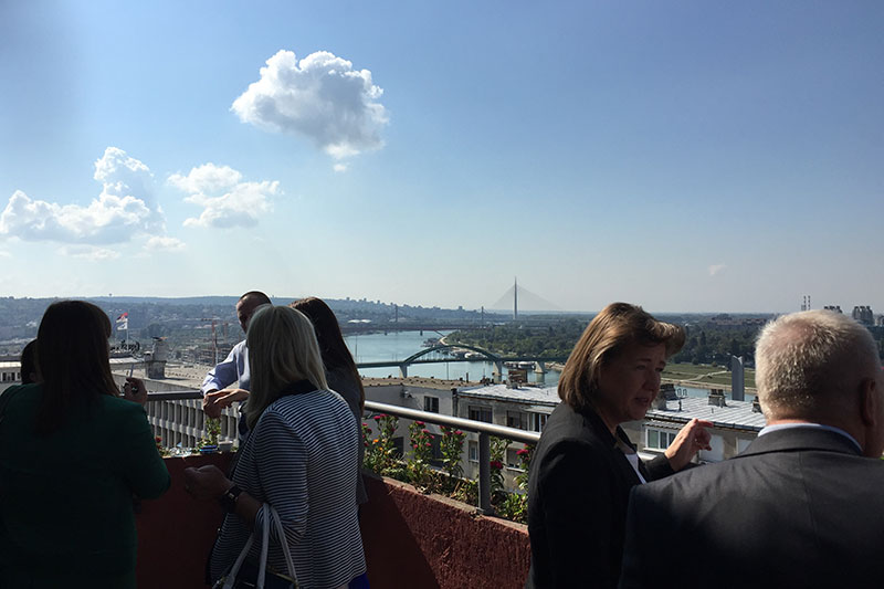 Participants chat during the coffee break, with views over the city of Belgrade in the background