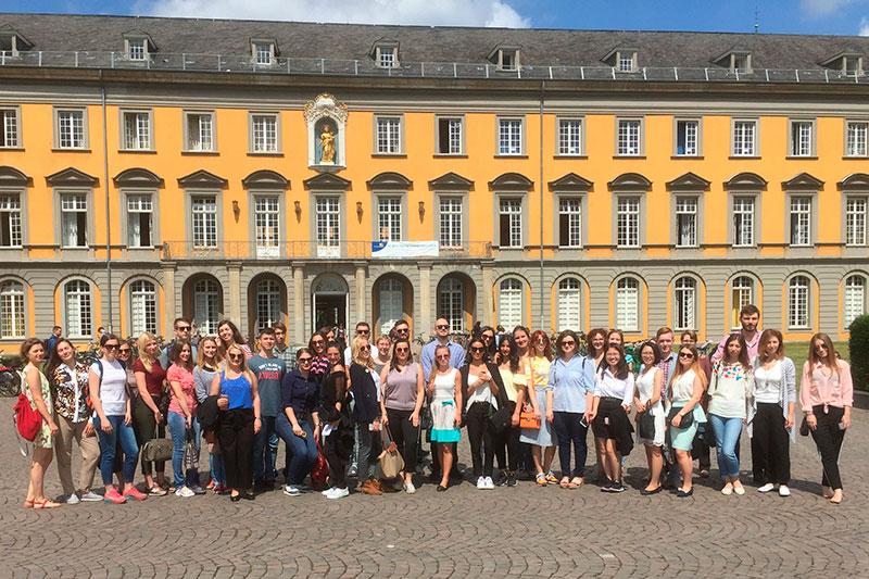 """Teilnehmerinnen und Teilnehmer der siebten """"IRZ-Sommerschule Deutsches Recht"""" vor der Rheinischen FriedrichWilhelms-Universität Bonn"""
